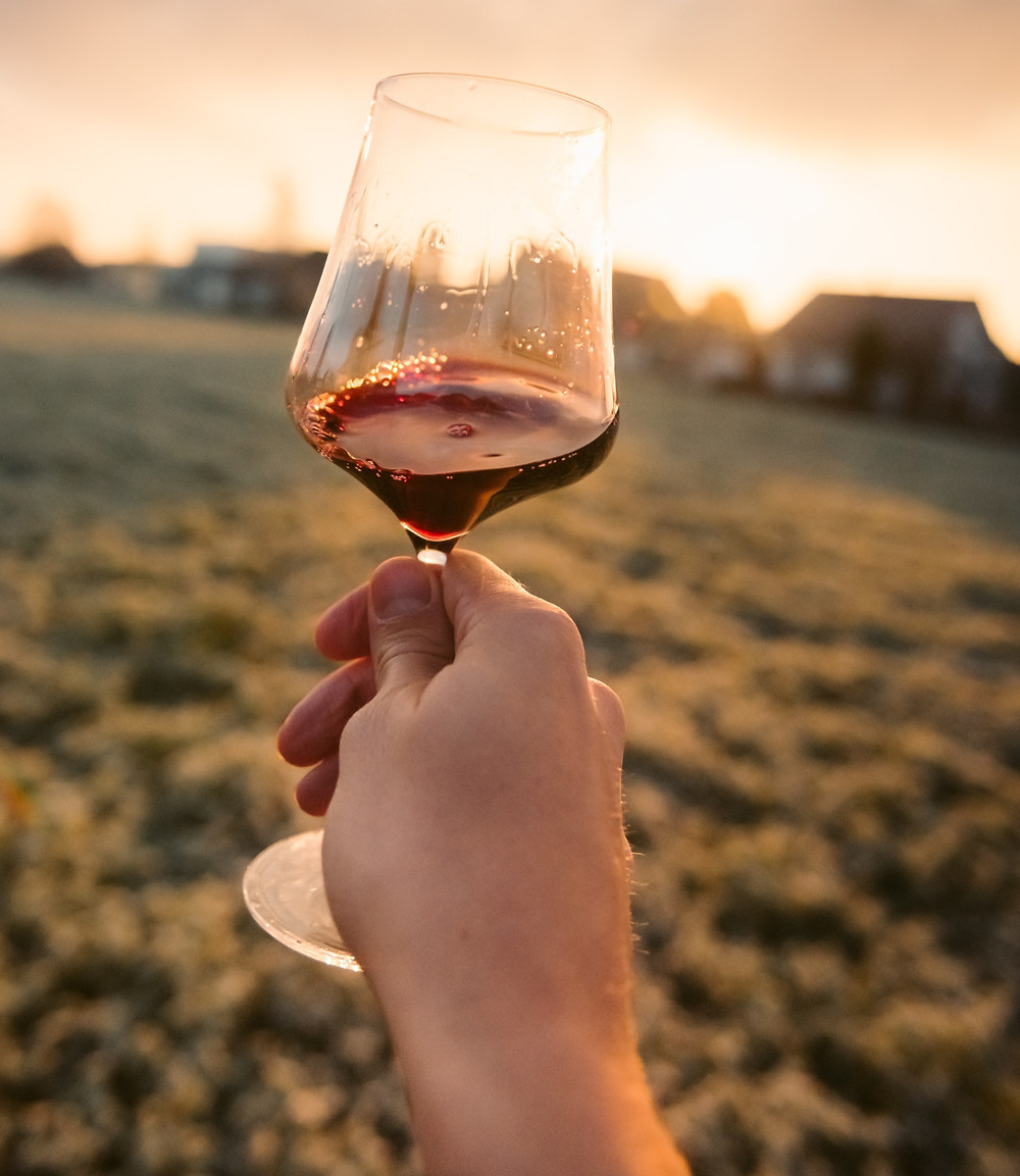 raising a glass with wine to a sunset background