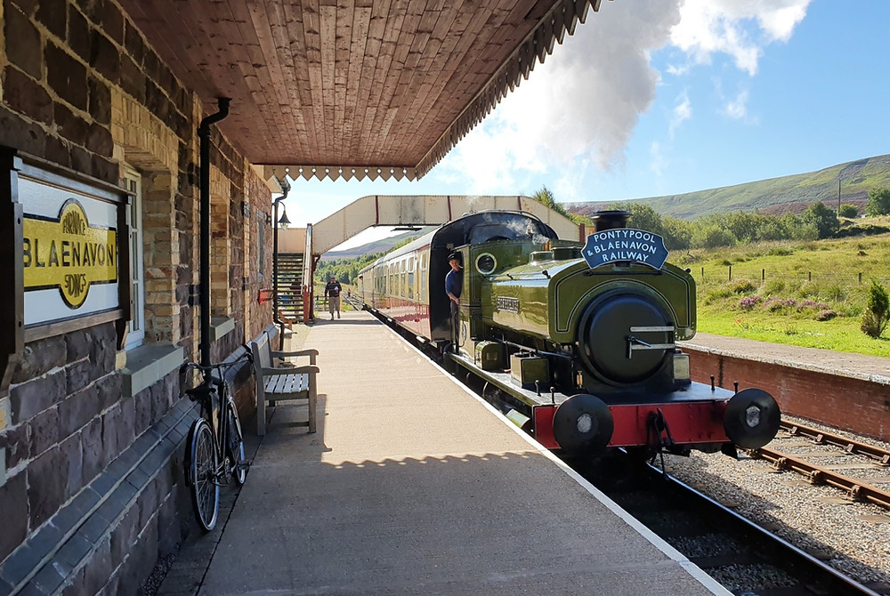 Green steam locomotive Rosyth steams into Furnace Sidings station past the stone-clad building on a bright morning