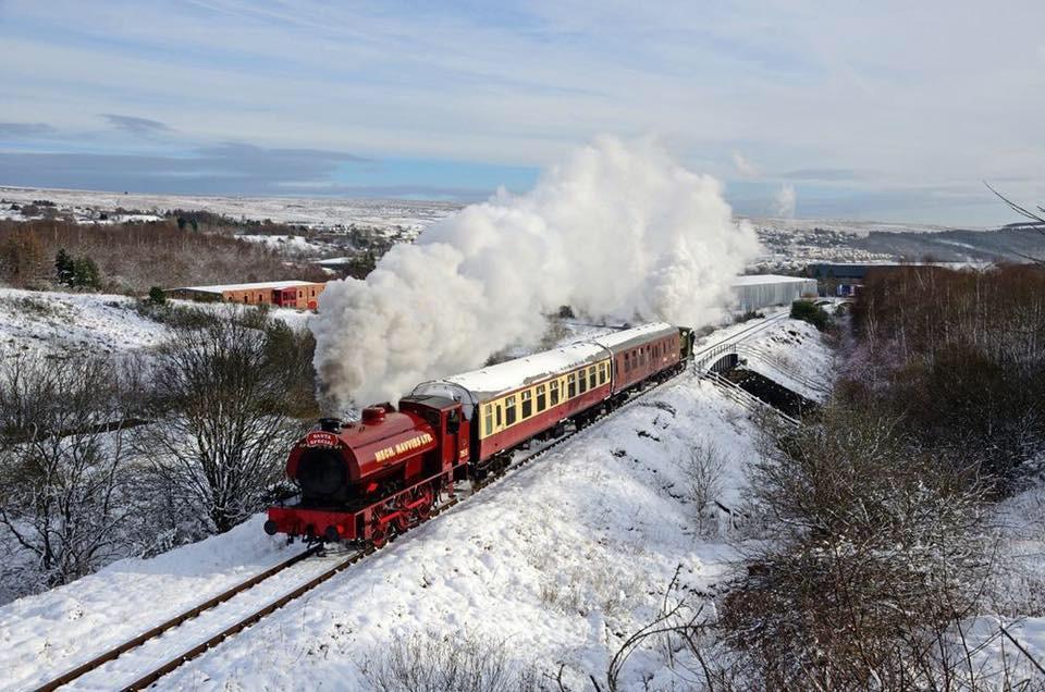 Steam locomotive 71515 charging past a snowy Rhymney Brewery