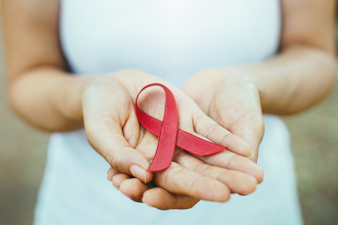 Hands holding red ribbon for AIDS Awareness