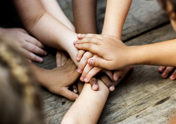 Diverse hands are join together on the wooden table