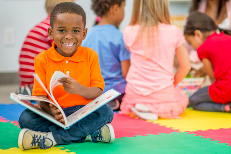 smiling preschool boy reading a book.png