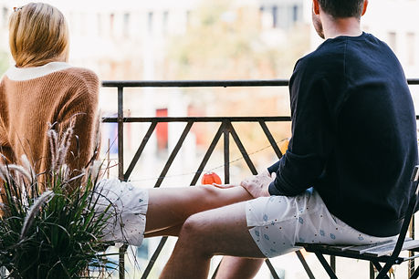 girl and guy in boxer shorts sitting on balcony
