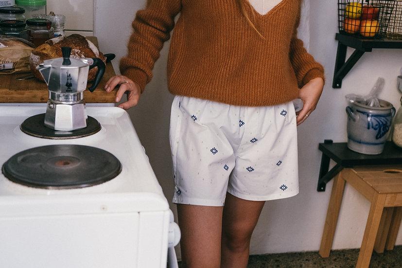 girl in kilim rug boxer shorts making coffee