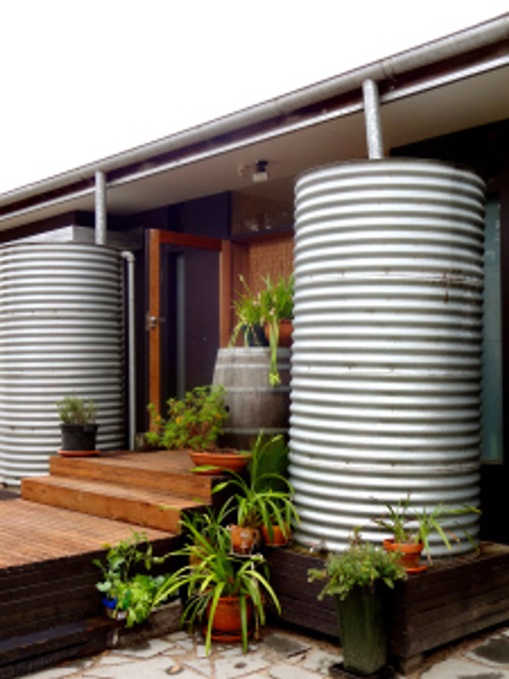 back entrance to the house - 1000 liter rain cisterns with water so lovely you can drink right from them