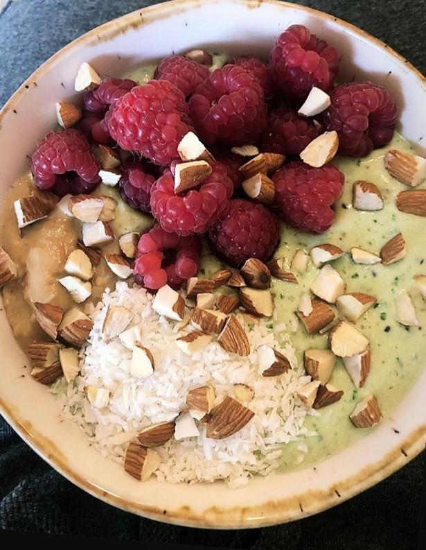 grønn smoothiebowl med spinat, kiwi, cottage cheese, banan, styrk melk. toppet med mandler, bringebær, kokos og penøttsmør.