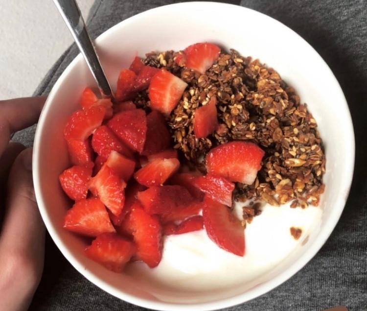 Hjemmelaget granola og jordbær over gresk yoghurt.