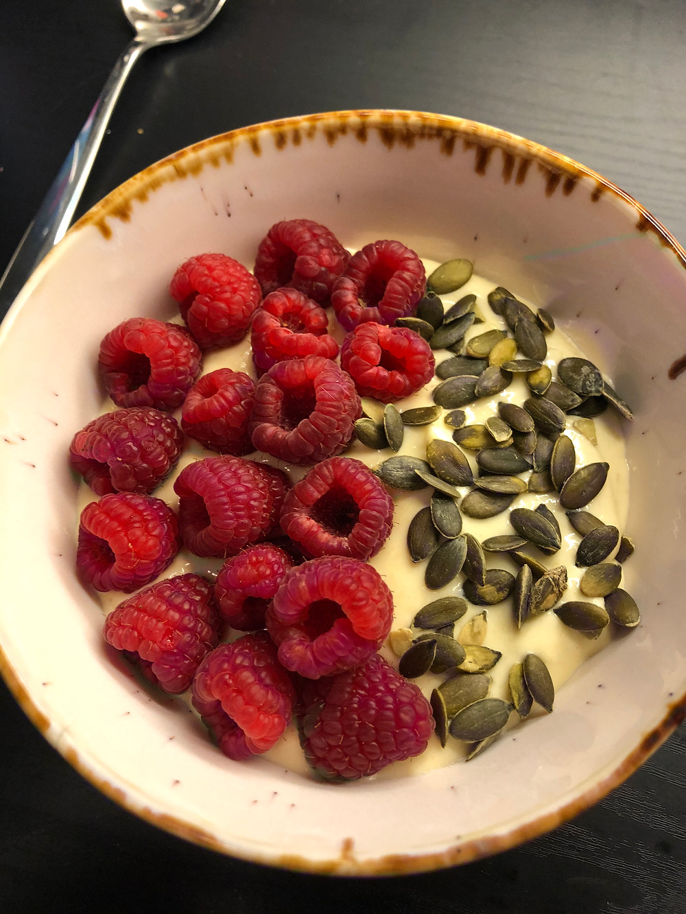 Mango med naturell yoghurt, banan og bodylab whey 100 mango passion. Toppet med bringebær og gresskarkjerner.