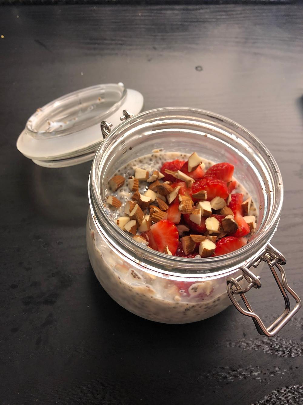 chiagrøt chiapudding laget med chiafrø, melk og havregryn. toppet med mandler og jordbær
