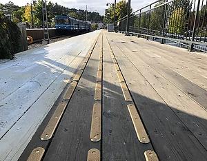 En lång rad av taktilt ledstråk av mässing stavar är monterat på en folktom tågperrong av trä i Stockholm.