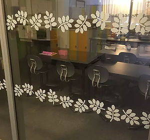 Bilden föreställer ett glasparti som försetts med ljusgrå blad som kontrastmarkering i två rader.