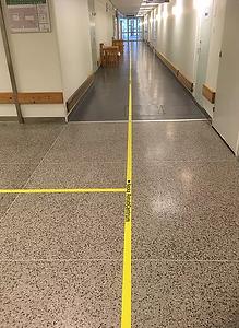 Ett gult visuellt ledstråk med hänvisnings markering och pil är monterat på ett grått terazzogolv på ett sjukhus.