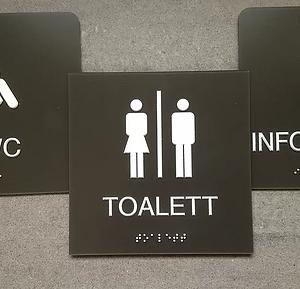 Svarta taktila skyltar med vit text och punktskrift för toalett, RWC och information är presenterade mot en grå bakgrund.