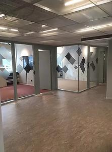 Kontorslokal där glaspartierna försetts med stora fyrkanter i olika sorters grå nyans som dekor och kontrastmarkering.