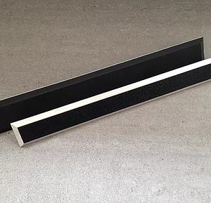 Två svarta taktila ledstavar i polyuretan presenteras mot en grå bakgrund.