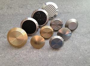 Tio olika stoppmarkeringar i rosfritt stål och mässing presenteras mot en grå bakgrund. Stoppmarkeringarna är mellan 25-35mm i diameter och har olika mönster på ovansidan.