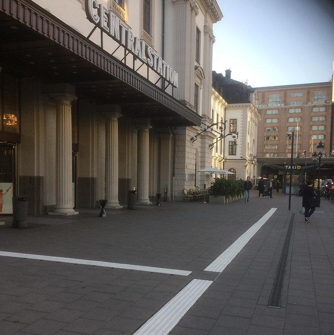 Bild över Stockholms Centralstation man kommer gående och taktilt ledstråk på marken.