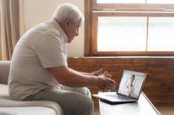 Elderly 70s man seated on sofa make dist
