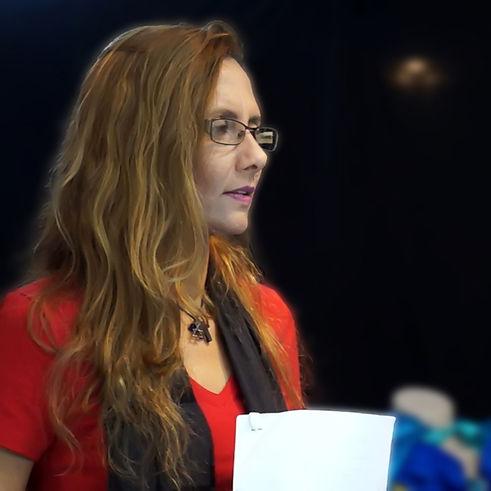 Close da preparadora de elenco dando aula. Ela usa óculos e segura o texto em suas mãos. Seus cabelo