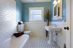Clutter free bathroom with white tiles and mid-blue walls