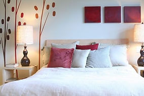 Bed with white bedding and pink and white pillows
