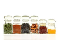 Row of clear jars containing spices and herbs