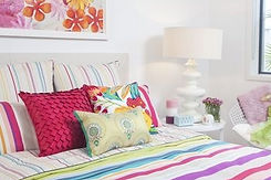 Large bed with stripey duvet and multi-coloured pink pillows and cushions