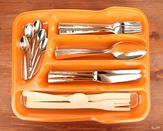 Orange cutlery tray with spoons, knives and forks