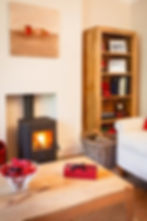 Wood burner in warm living room with bookcase