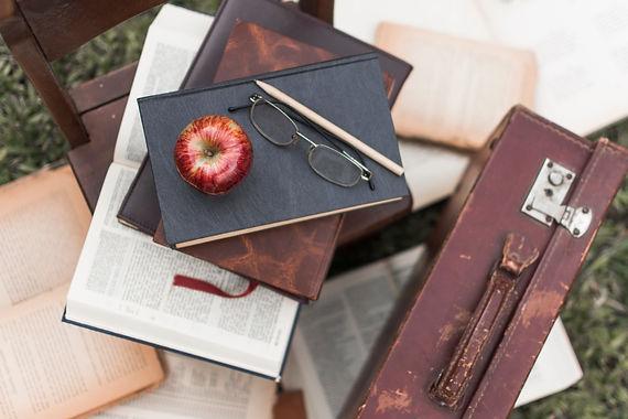 Libros, gafas y manzana.