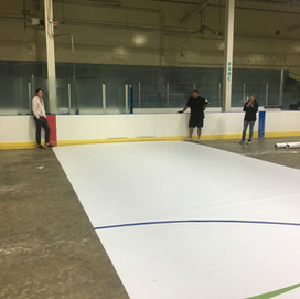 Easy Sheet being put down at hockey rink.