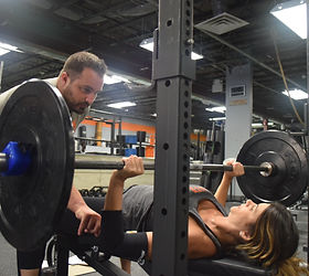 Woman bench pressing at NY Strong