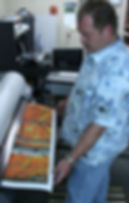 A man printing a giclee on canvas