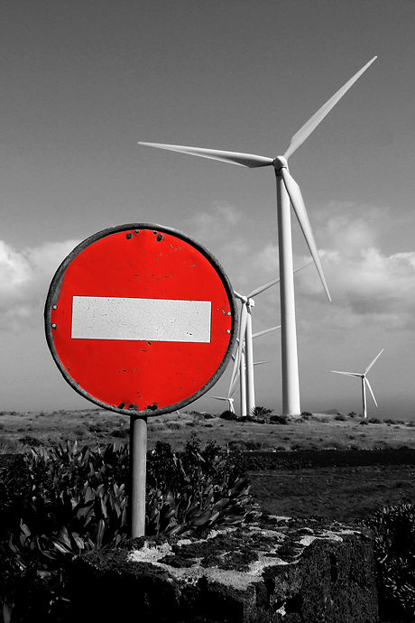 Wind turbines near a road sign for forbi