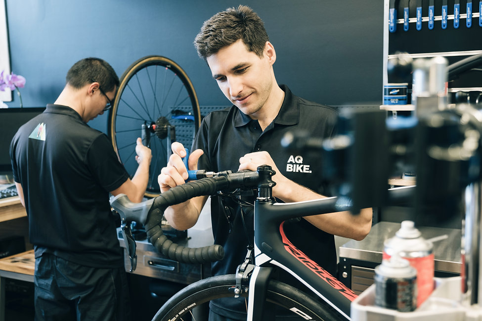 AQ bike mechanics servicing bicycles in the workshop