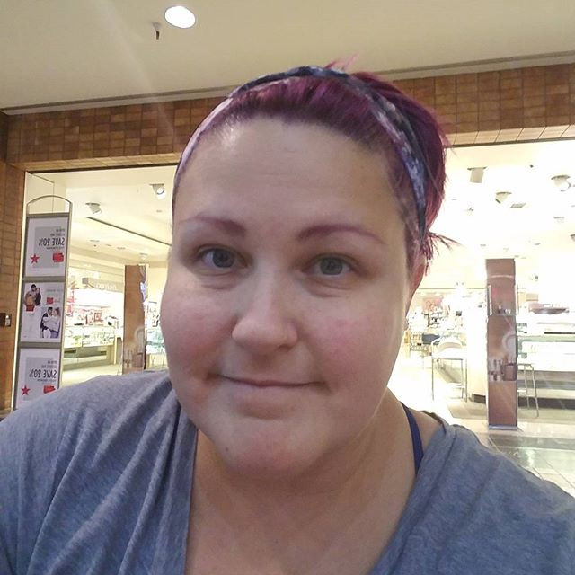 A woman with pink hair and mo make up is seated in front of Macy's at the mall. She is shabbily  dressed in a gray oversized t-shirt and floral headband.