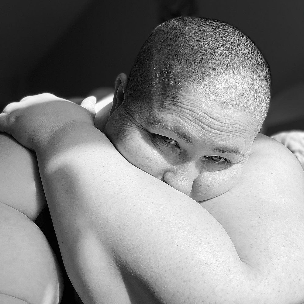 The author, a fat white non-binary person with a shaved head hugs themselves as they gaze to the left of frame.
