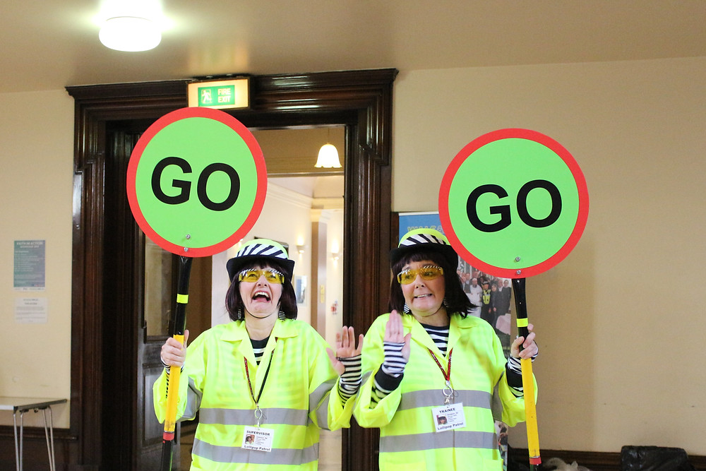 Two actors dressed as lollipop ladies holding a GO sign.
