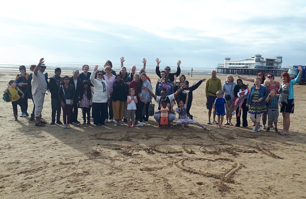 A large mixed group of parents, children and other adults on a day trip at Weston-super-Mare.