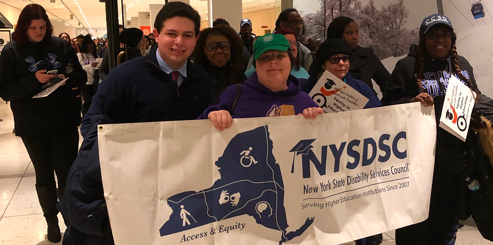President Ostro standing with fellow advocates holding a NYSDSC banner at a rally for enhanced disability services