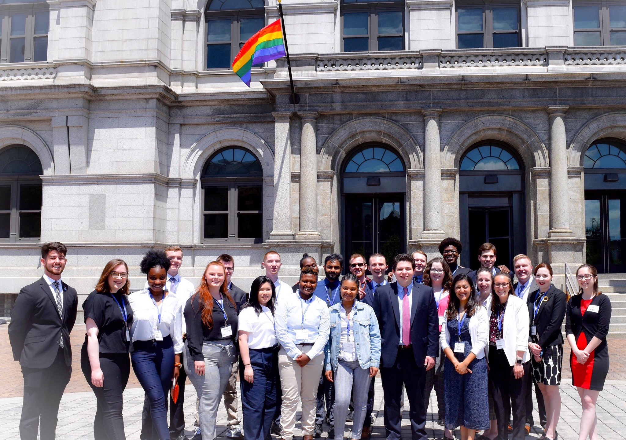 All SUNY Voices student attendees standing together outside of SUNY Plaza in front of a rainbow pride flag
