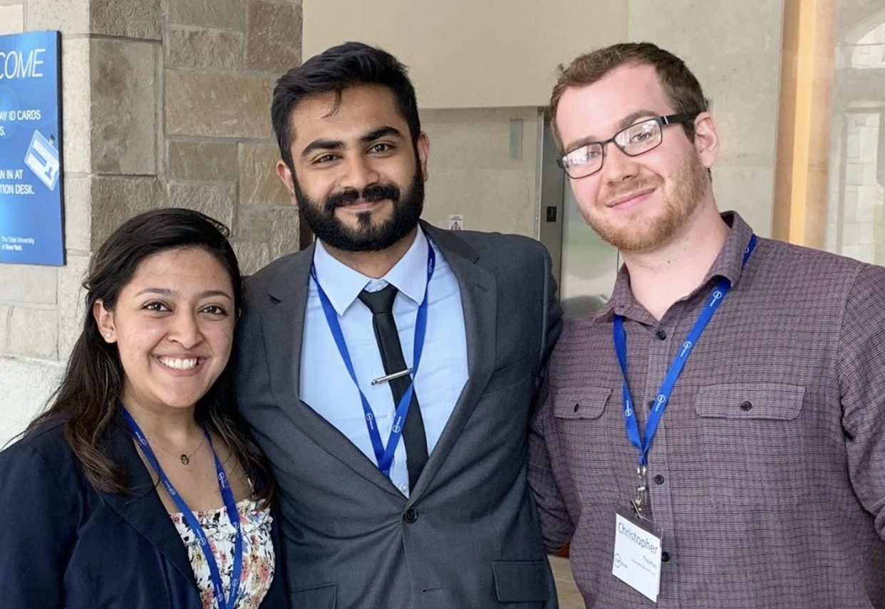 Three student government presidents standing together, smiling at camera