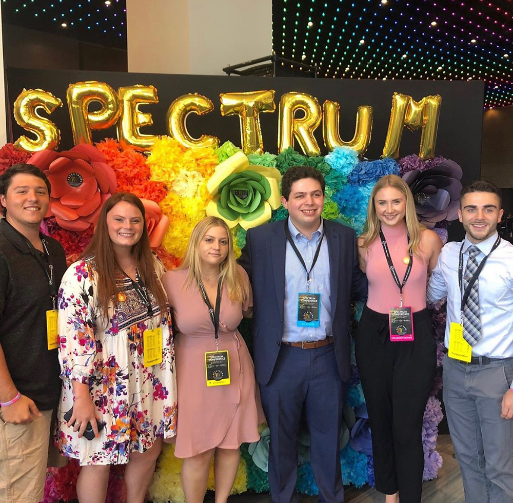 "Members of the Student Assembly Executive Committee standing in front of a sign that has a rainbow of flowers and the word ""SPECTRUM"" in golden balloon letters"