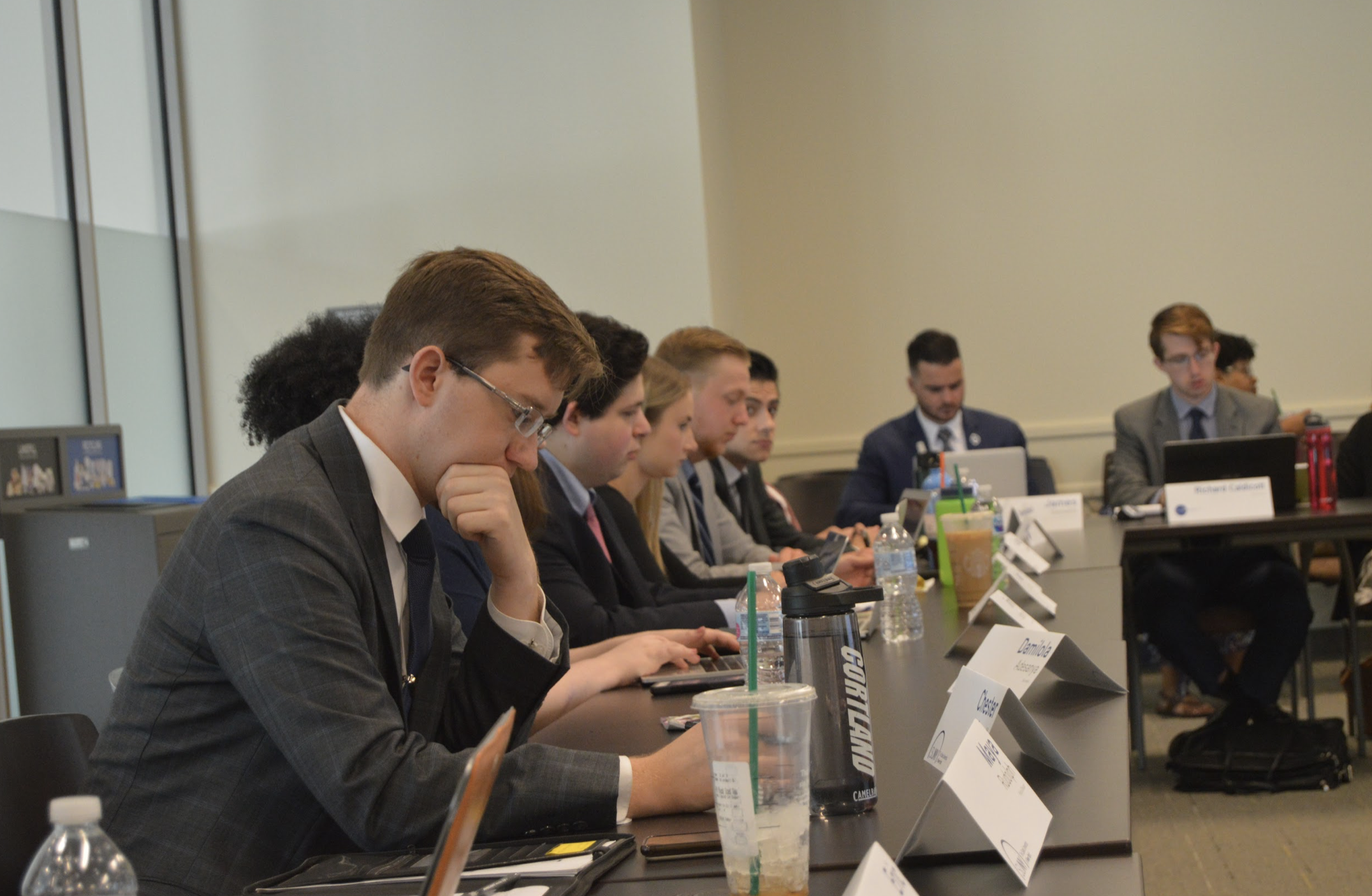 Members of the Executive Committee working on laptops in a board room at the University at Albany