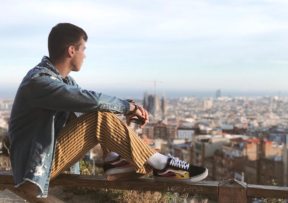 Vice Chair Dylan Marshall on one of his international trips, sitting and looking off to a skyline