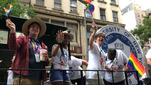 Student Assembly members Brad Hershenson and Kaitlyn Trusty waving from atop the SUNY Pride float in NYC, alongside other SUNY attendees