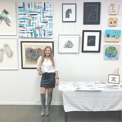 Artist standing in front of artworks in a gallery.jpg