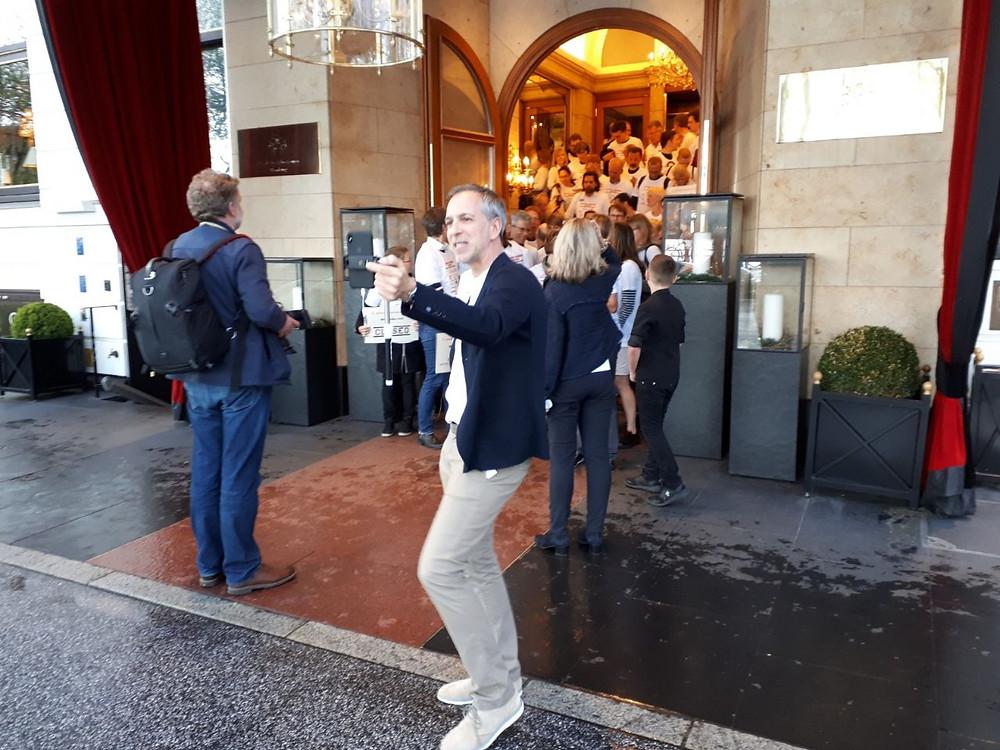 Markus Tirok geht auf Facebook live während die Spendenläufer den Hoteleingang für das Gruppenbild blockieren.