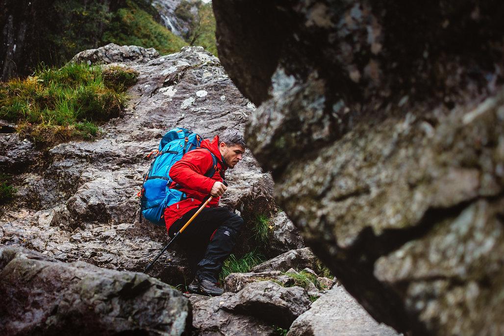 Mountain climber scramblking between large rocks.