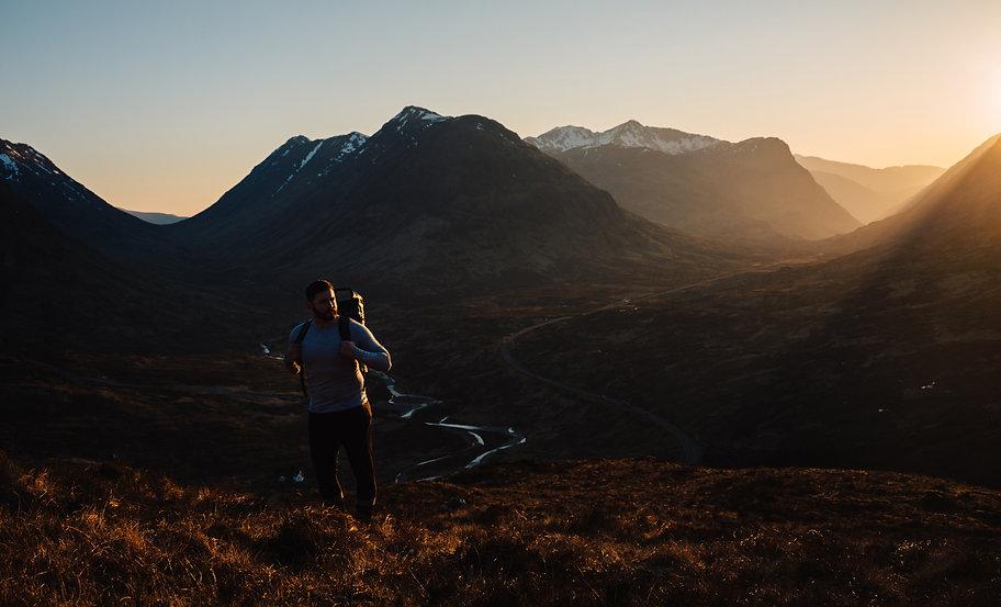 Man hiking at sunset in the Glencoe mountains, Scotland